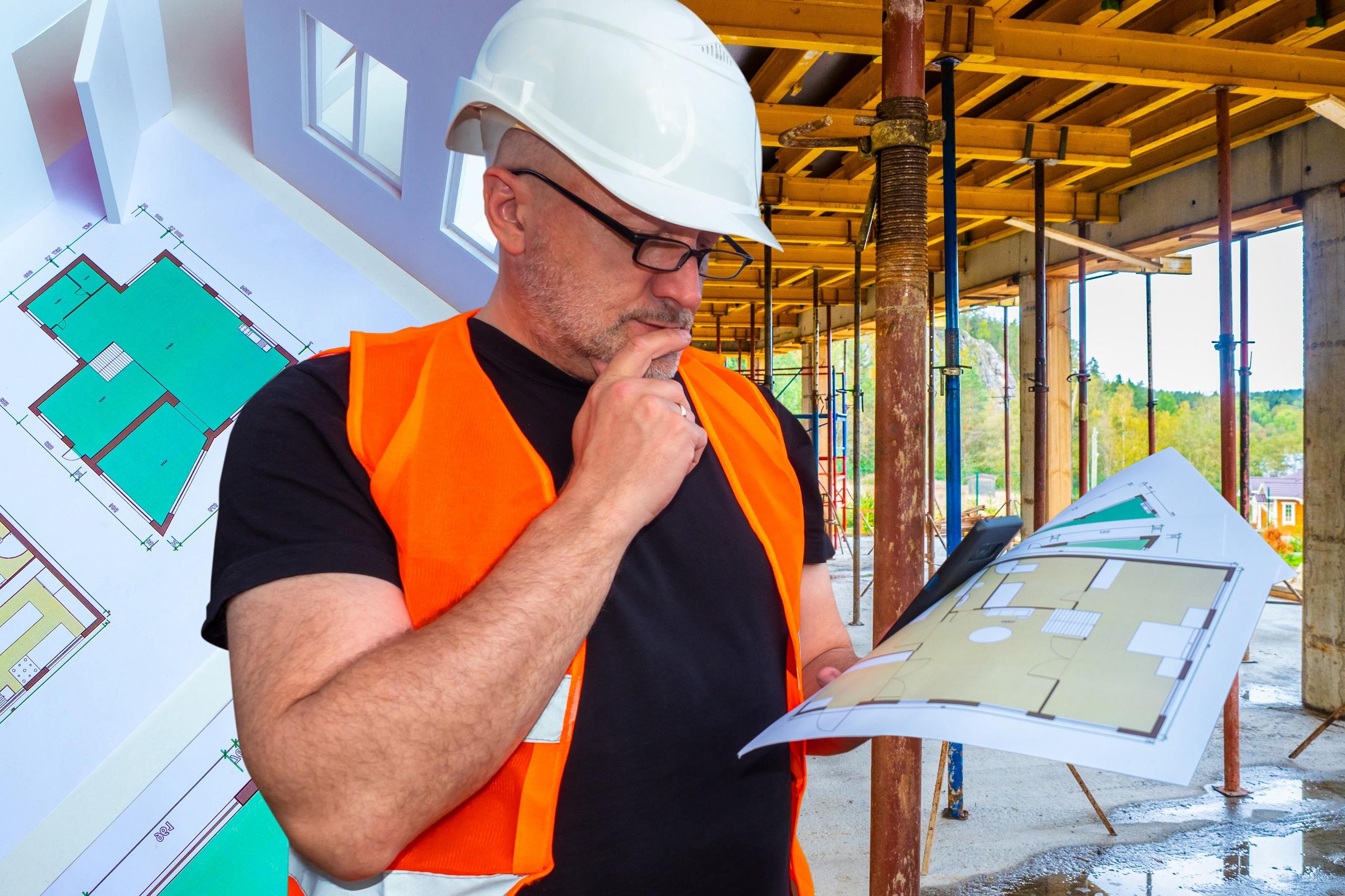 image d'un architecte sur un chantier avec un plan dans les mains